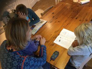 Kvinne med TENS-apparat som hjelper to barn med lekser