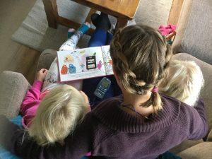 Kvinne med tenselektroder i nakken som har lesestund for to barn i armkrokene