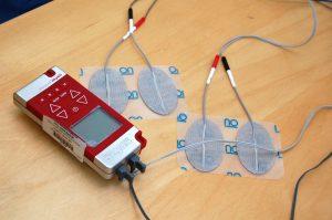 Rødt TENS-apparat med elektroder på et bord