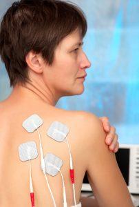 Kvinne med TENS-elektroder på skulderbladet