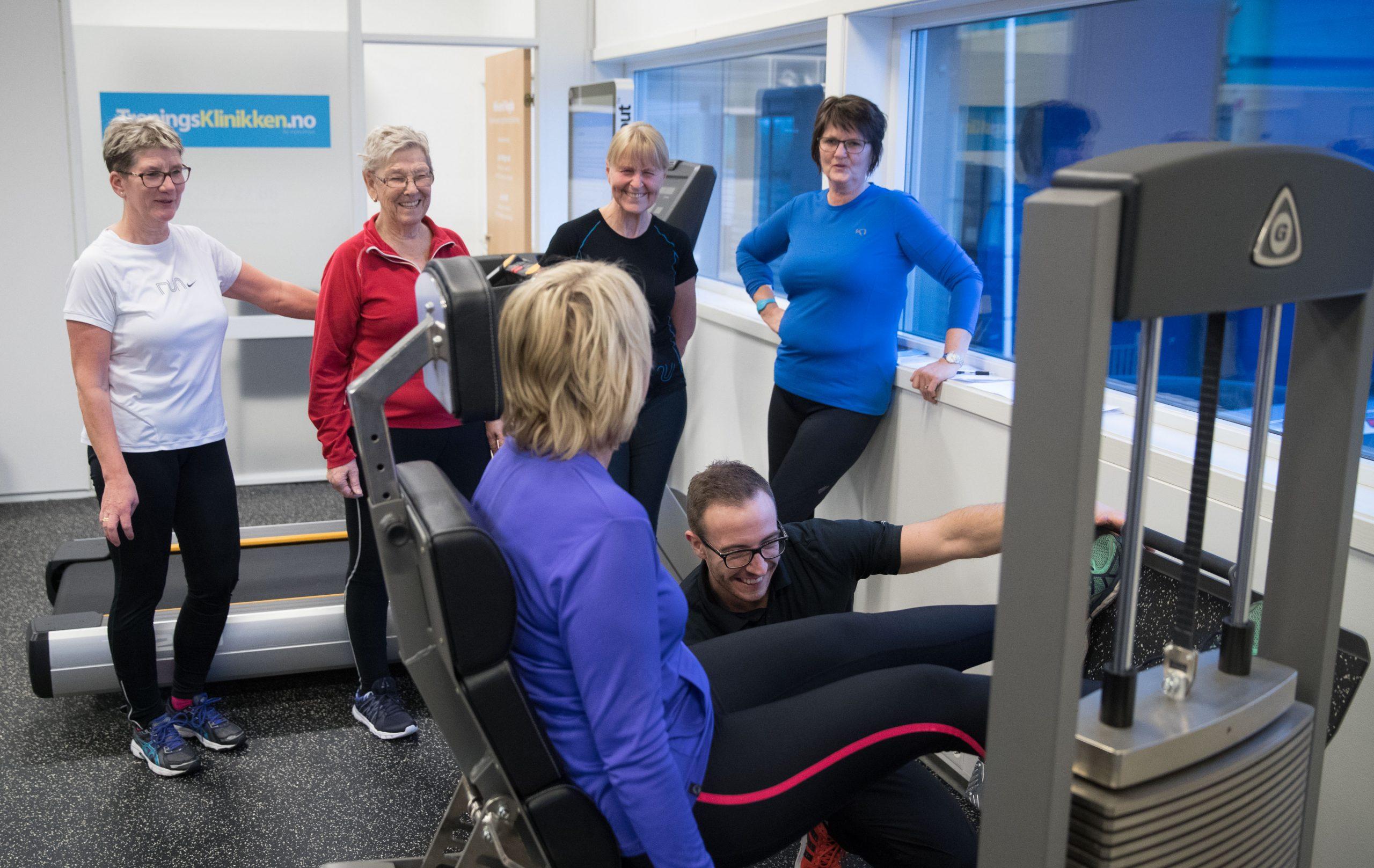 Fire deltager står rundt beinpressapparat hvor mann hjelper en kvinne
