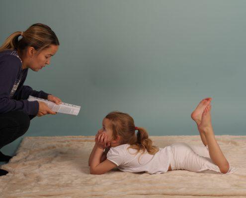 Kvinne på huk leser fra bok for et barn som ligger og følger interessertmed