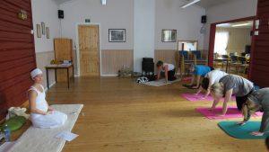 Yogainstruktør foran elever i yogaposisjoner