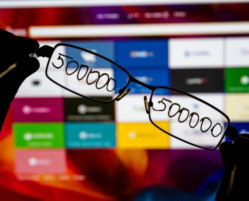 Briller med skriften 500.000 i foran en PC-skjerm