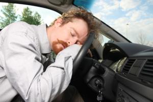 Mann sover på rattet i en bil