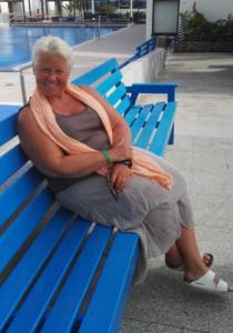 Kvinne sittende på en blå benk foran et utebasseng