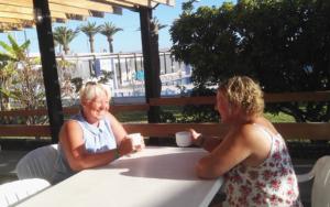 To kvinner snakker mens de tar en kaffekopp i solen