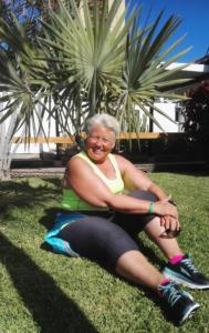 Kvinne i treningstøy sittende foran et palmetre