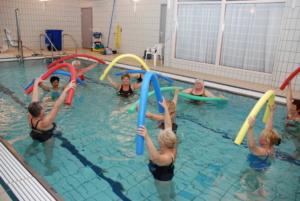 Gruppe damer i basseng med fargerike pøller i været