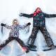 Stor og liten person ligger i snøen og lager engler