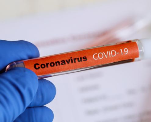 Hanskehånd holder reagensglass med påskrivten coronavirus Covid-19