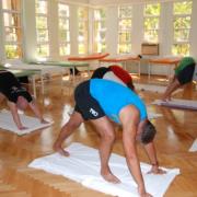 En gjeng trener yoga innendørs i gymsal