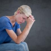 Kvinne hviler albuene på knærne og har pannen mot hendene