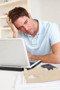 Mann sitter ved PC og er bekymret