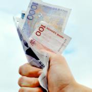 Hånd knuger norske pengesedler