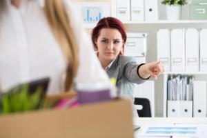 Kvinnlig sjef peker på døren og viser en kvinne med eske med saker veien ut