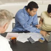 Ektepar sitter rådvilleved laptop hos en rådgiver