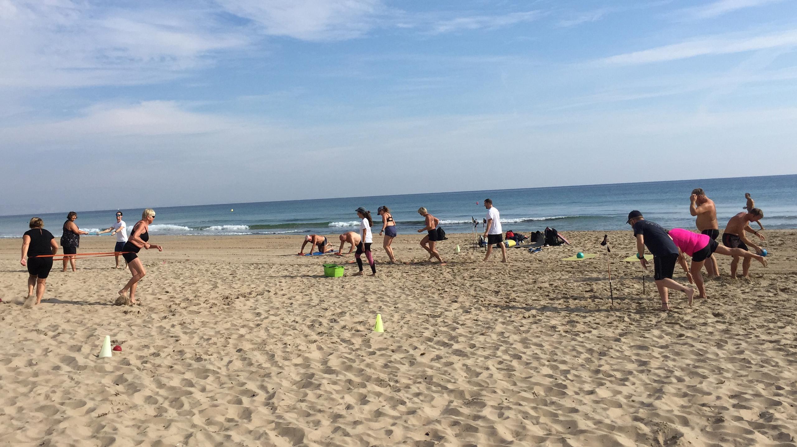 En gjeng som trener ulike øvelser på en sandstrand