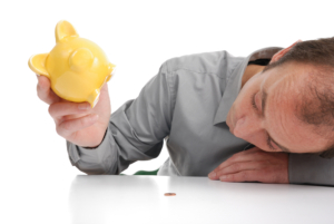Mann får ut en liten mynt fra en gul sparegris