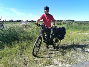 Mann står ved el-sykel i et dansk naturlandskap