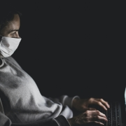 Kvinne med munnbind sitter i mørket og ser på laptop i fanget