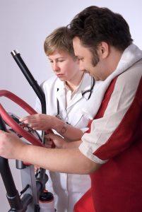 Mann på ergomertersykkel sammen med lege ved siden av