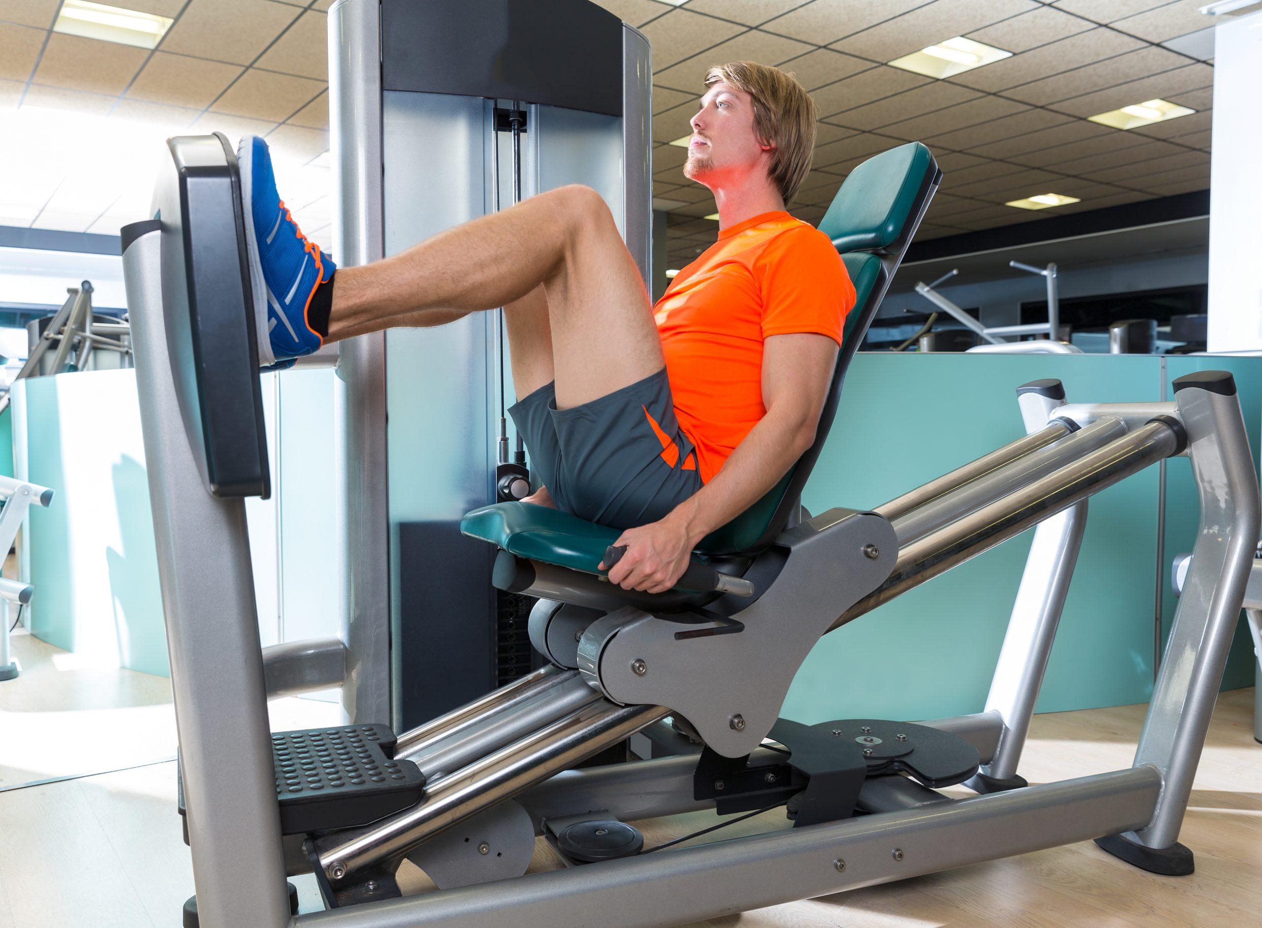 Mann trener beinpress i treningsapparat