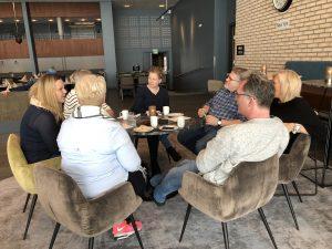 Gruppe mennesker rundt et bord inne prater