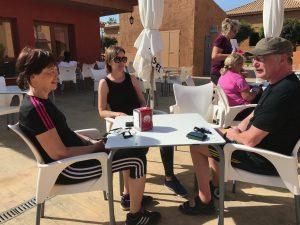 Tre mennesker ute rundt et bord prater