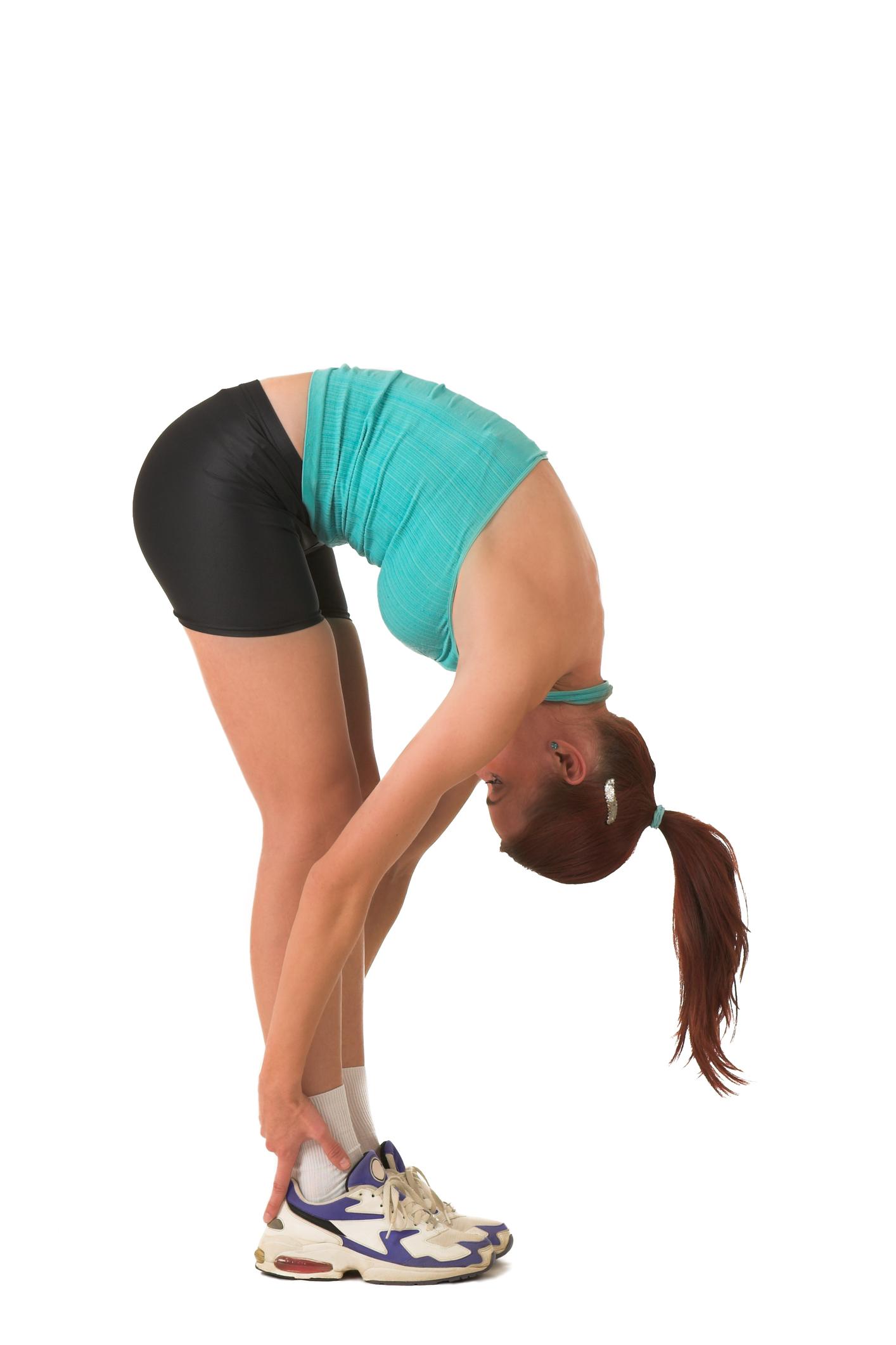 Kvinne med bøyd rygg tøyer bakside av ben og korsrygg