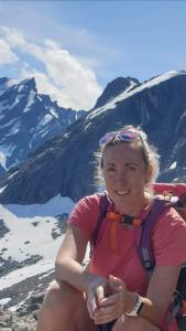 Caroline Rørstad med fjelltopper med snø på i bakgrunnen