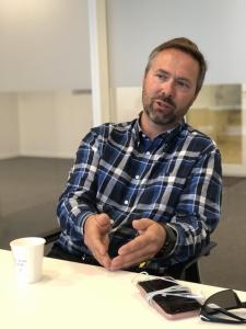 Dr. Gunnstein Bakland i samtale ved et bord