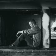 Svarthvittbilde mann sitter og ser trist ut