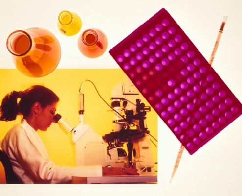 Forsker ser i mikroskop med reagensrør rundt