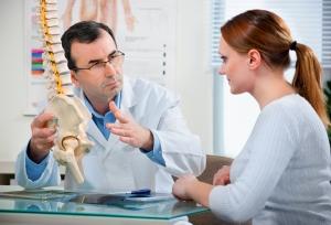 Mannlig lege med skjellett av bekken og ryggrad forklarer ting for ung kvinnlig pasient