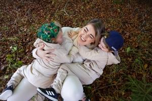 Ung kvinne leker på bakken med to barn oppå seg