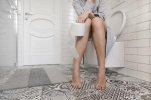 Bena til en kvinne som sitter på toalettet med dorull i hånden
