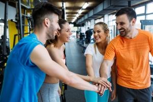 Fire personer på treningssenter samler hendene i midten for å støtte hverandre