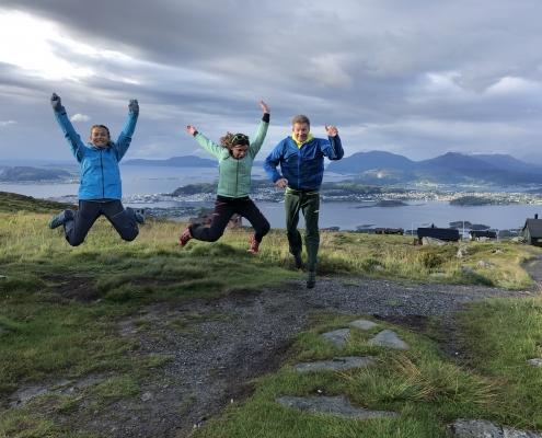 Tre personer hopper med flott utsikt av hav og fjell i bakgrunnen