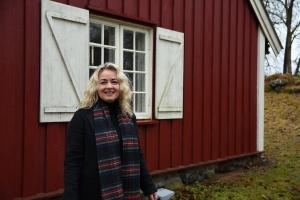 Lillann Wermskog utenfor en rød stue med rutete vinduer