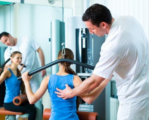 Fysioterapeut veileder kvinne med treningsapparat