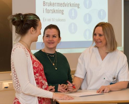 Sykepleier i samtale med to brukere