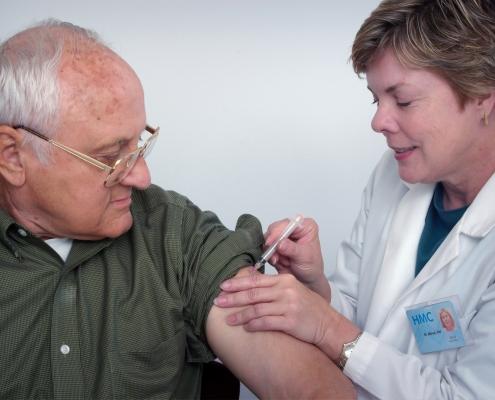 Kvinnlig lege vaksinerer en eldre mann