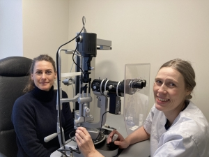 Øygunn Utheim og pasient ved øyeundersøkelsesutstyr