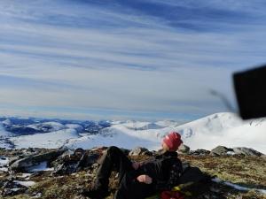 Thor-Elvin Jøtulhaug i turklær ligger og ser på utsikt med snødekte fjell