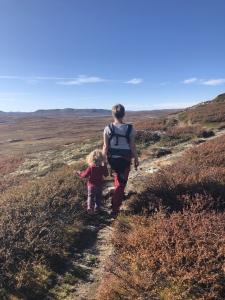 Kvinne på fjellvidde med bæresele leier et barn gjennom lyng