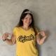 Kvinne med tiara peker på T-skjorteskriften Go'nok