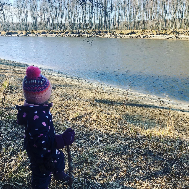 Lite barn med stokk ved et vann
