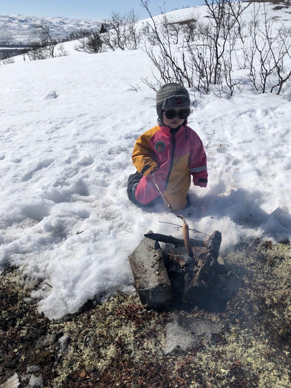 Lite barn i vinterdress griller pølse på bål