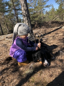 Et barn setter store pinnehorn på en liggende hund